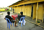"""Two men relax at a table at a brothel, as a woman walks to her room in Kampong Chhnang Province, Cambodia.  When Randa Lee first returned to her country, she agonized over the women trapped in such a life. """"A lot of girls had been kidnapped,"""" she says. """"A lot of parents were so sick they sold their daughters to be prostitutes.  Or sometimes the girls just did it to get money...It was a shame on the country."""".."""