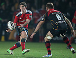 Fly-half Ian Keatley of Munster Rugby offloads the ball as he is confronted by Lewis Evans of Newport Gwent Dragons.<br /> <br /> Guiness Pro 12<br /> Newport Gwent Dragons v Munster Rugby<br /> Rodney Parade<br /> 21.11.14<br /> ©Steve Pope-SPORTINGWALES
