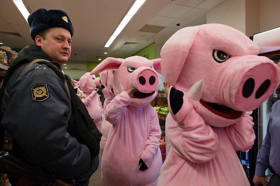Moscow, Russia, 03/03/2011..Police called by store management watch as members of health campaign group Pigs Against check the sell-by dates and quality of food in a city centre supermarket while dressed in pig costumes.
