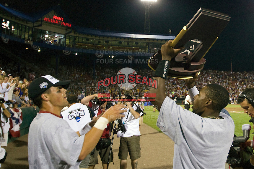 South Carolina teammates Whit Merrifield (L) and Jackie Bradley Jr (R) raise the championship trophy following Game Two of the NCAA Division One Men's College World Series Finals on June 29th, 2010 at Johnny Rosenblatt Stadium in Omaha, Nebraska.  (Photo by Andrew Woolley / Four Seam Images)