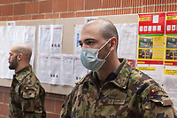 """Switzerland. Canton Ticino. Rivera. Monte Ceneri military base. Due to the spread of the coronavirus (also called Covid-19), the Federal Council has categorised the situation in the country as """"extraordinary"""". The army was called upon to provide logistical support and to offer its skills in terms of medical assistance (ambulances, field hospital, tents, nurses,..). The militia soldiers from medical troops were called by the Swiss army for the first time since World War II. Under the country's militia system, professional soldiers constitute a small part of the military and the rest are conscripts or volunteers aged 19 to 34 (in some cases up to 50). Two soldiers wait to wash their hands before entering the refectory. A bald man wears a mask in front of his mouth. On the wall, the Coronavirus poster explains how to prevent from getting the disease. The measures are: Keep your distance, wash your hands thoroughly, avoid shaking hands, cough and sneeze into a tissue or the crook of your arm, stay at home if you have fever, always call ahead before going to the doctor's or the emergency department. Monte Ceneri is a mountain pass in the canton of Ticino. It connects the Magadino plain and the Vedeggio valley across the Prealps. 2.04.2020 © 2020 Didier Ruef"""