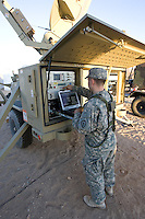 Model-released Army soldier works on SATCOM AN/TSC-167B DATAPATH network antenna system at National Training Center, Fort Irwin, CA.  SPC Timothy Saari, HHC 2/35/25ID.