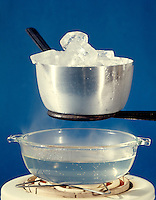 THREE STATES OR PHASES OF WATER<br /> Solid Ice, Vapor & Liquid<br /> Steam rises from water heated to boiling on an electric hot plate and condenses on cold aluminum metal pot filled with ice cubes.