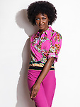 Beautiful smiling young african american woman wearing pink floral top and pants. Fashion photo isolated on white background. Image © MaximImages, License at https://www.maximimages.com
