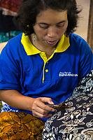 Yogyakarta, Java, Indonesia.  Woman Applying Wax to Floral Design on Batik Cloth.