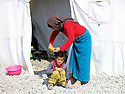Iraq 2015  <br /> In the camp of Berseve, Yezidi woman doing a haircut to her child in front their tent  <br /> Irak 2015 <br /> Au camp de Berseve, femme yezidi coupant les cheveux de son enfant devant leur tente.