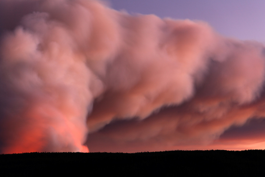 Smoke and flames of forest fire burning on Central Plateau at sunset as viewed from Hayden Valley, September 24, 2009, Yellowstone National Park, Wyoming, USA