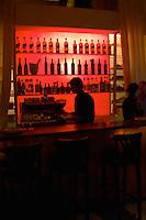 The bar of the restaurant CRU in Montevideo, supposedly one of the better and trendier restaurants in the city. The bar is back lit in red, bottles in silhouette, Johnnie Walker whiskey and other and the bar tender is standing by the espresso machine. Montevideo, Uruguay, South America