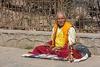 Nepal, Kathmandu, Swayambhunath.  Man Sitting with his Prayer Beads.