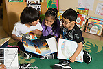 Education Preschool 4-5 year olds group of two boys and a girl having conversation over picture books