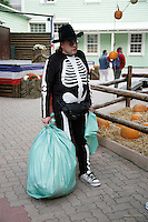 Italy. Province of Veneto. Castelnuovo del Garda. As a preparation for Halloween, a sweeper is wearing a dead human skeletton costume and a hat with skull. He is carrying in his hands two green plastic bags full of rubbish. Gardaland is the biggest amusement park in Italy and one of the largest in the whole of Europe. © 2006 Didier Ruef