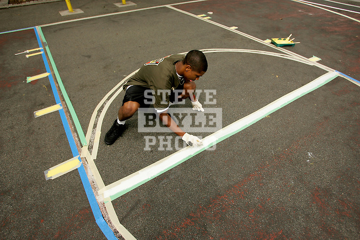 Dexter Strickland paints a line on a basketball court in New York City as part of his volunteer service on August 31, 2006.  The players were in town for the Elite 24 Hoops Classic, which brought together the top 24 high school basketball players in the country regardless of class or sneaker affiliation.