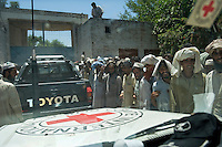 A crowd of refugees from Swat district gather at a distribution centre where they hope to receive food and clothing as Red Cross/Red Crescent (ICRC) vehicles arrive. The Pakistani government began an offensive against the Taliban in the Swat Valley in April 2009, which led to a major humanitarian crisis. Up to two million civilians were estimated to have been displaced by the fighting.