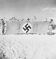 BNPS.co.uk (01202) 558833. <br /> Pic: TankMuseum/BNPS<br /> <br /> Pictured: Capturing the flag. <br /> <br /> A Union Jack flag flown in defiance during the Siege of Tobruk is being displayed for the first time alongside a Nazi swastika flag captured during its liberation.<br /> <br /> The Allies held out for eight months in the face of an Afrika Corps onslaught until they were freed by the 8th Army in November 1941.<br /> <br /> The German commander Erwin Rommel was surprised by the aggressive attack, codenamed Operation Crusader, and forced to retreat at a pivotal juncture of the North African campaign.<br /> <br /> In the ensuing chaos, the swastika flag was captured from an 88mm flak gun locker by the advancing 8th Royal Tank Regiment.<br /> <br /> The flags will go on show from next month as part of the new World War Two: War Stories exhibition at the Tank Museum in Bovington, Dorset.