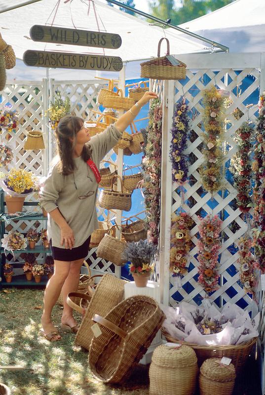 Vendor arranging baskets at Corvallis Fall Festival, Oregon.