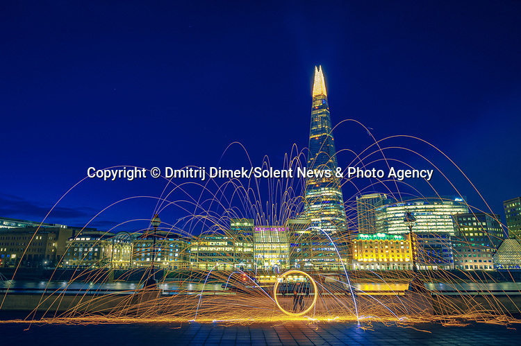 """Pictured:  Central London<br /> <br /> Amazing photos show sparks illuminating British landmarks as they fly from what appears to be a disc of colourful light.  This unique effect is the result of long-exposure night-time shots of a whisk stuffed with steel wool, which is set alight and spun at the end of a metal chain.<br /> <br /> Amateur photographer Dmitrij Dimek is passionate about what he calls 'light paintings', and took these photos at castles, beaches and other settings around Essex and London.  The 38 year old, who grew up in Poland but now lives in Southend-on-Sea, Essex, said: """"When I first found out about light painting with steel wool, I thought it was an outstanding way to connect with photography.  SEE OUR COPY FOR DETAILS.<br /> <br /> Please byline: Dmitrij Dimek/Solent News<br /> <br /> © Dmitrij Dimek/Solent News & Photo Agency<br /> UK +44 (0) 2380 458800"""