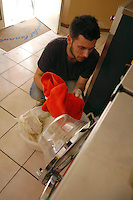 Giovani studenti e neolaureati lavorano in una lavanderia a gettoni..Young students and graduates working in a laundromat..