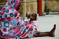 TANZANIA Zanzibar, Stone town, mother feeds baby with milk bottle/ TANSANIA Insel Sansibar, Stonetown, Mutter gibt ihrem Kind die Milch Flasche
