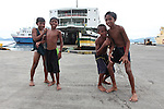 Fresh from a swim, local boys play on the docks in the town of Dapitan, on Mindanao island, Philippines. June 16, 2011.