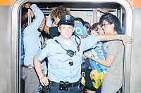 A policeman blocks further passengers from entering a packed subway train after the end of activities at the Democratic National Convention at the Wells Fargo Center in Philadelphia, Pennsylvania, on Wed., July 27, 2016.