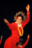 Woman wearing red muumuu performing a hula dance with a smile at the Merrie Monarch festival in Au'aina on the Big Island
