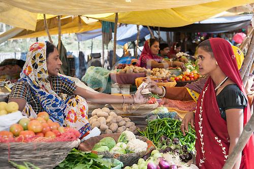 Rajasthan, India. Sawai Madhopur. Woman paying at a market stall selling vegetables.