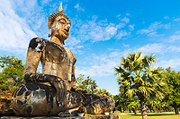 Wat Maechon beautiful stone Buddha statue perspective during morning golden hour, in Sukhothai Historical Park, Thailand