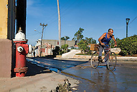 Red fire hydrant and a mature man cycling in the streets of Trinidad, Sancti Spiritus, Cuba.