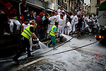 Two cleaning service workers clean the streets before the second run of the bull of the San Fermin Festival, on July 8, 2012, in Pamplona, northern Spain. The festival is a symbol of Spanish culture that attracts thousands of tourists to watch the bull runs despite heavy condemnation from animal rights groups . (c) Pedro ARMESTRE