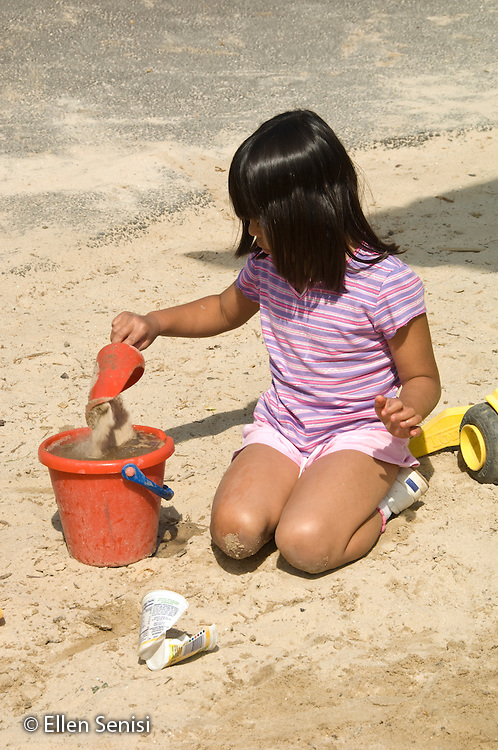 MR / College Park, Maryland.Center for Young Children, laboratory school within the College of Education at the University of Maryland. Full day developmental program of early childhood education for children of faculty, staff, and students at the university..Girl (5) plays by herself in the sand during recess..MR: Mos5.© Ellen B. Senisi