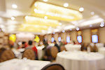 Abstract out-of-focus photo of people in a brightly lit restaurant