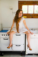 Young woman sitting on stove
