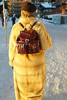 Switzerland. Valais. Crans Montana. Winter ski resort. A fancy woman, wearing a fur coat and an crocodile backbag ( shoulder bag) walks on the golf course.  © 2005 Didier Ruef