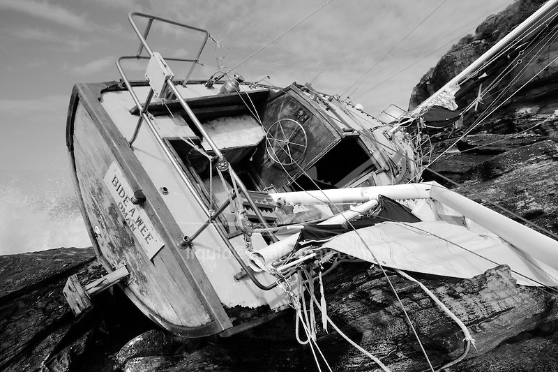 A 13m vessel, the Bide a Wee, on her side with holes in her timber hull, having been battered by heavy seas. The ketch  went aground  after leaving North Harbour under sail, it was  was marooned on the rocks at Grotto Point near Dobroyd Head at Balgowlah Heights, Sydney..A Maritime vessel and a police boat were both unable to reach two men on the ketch because of the wild waves and strong winds.An officer was winched down onto the stranded vessel from police helicopter PolAir to rescue the two..They were winched to safety and flown to Manly Hospital for treatment..The men did not appear to be injured...