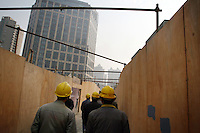CHINA. Shanghai. Construction workers walk through a construction site. Shanghai is a sprawling metropolis or 15 million people situated in south-east China. It is regarded as the country's showcase in development and modernity in modern China. This rapid development and modernization, never seen before on such a scale has however spawned countless environmental and social problems. 2008.