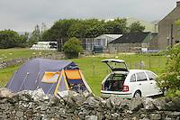 Car and tent in a farm field, Shap, Cumbria.