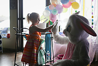 Alice Warren, 4, of Bella Vista high-fives the Easter bunny, Saturday, April 3, 2021 at the Oasis of Hope thrift shop Rogers. The Easter Bunny greeted guests for their prom dress and tuxedo sale. Staff gave away free Easter baskets, candy and books. Check out nwaonline.com/210404Daily/ for today's photo gallery. <br /> (NWA Democrat-Gazette/Charlie Kaijo)