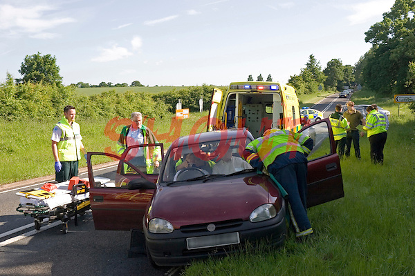 Firefighters and Paramedic crews attend a RTC and work together to release the trapped driver. Warwickshire UK. This image may only be used to portray the subject in a positive manner..©shoutpictures.com..john@shoutpictures.com