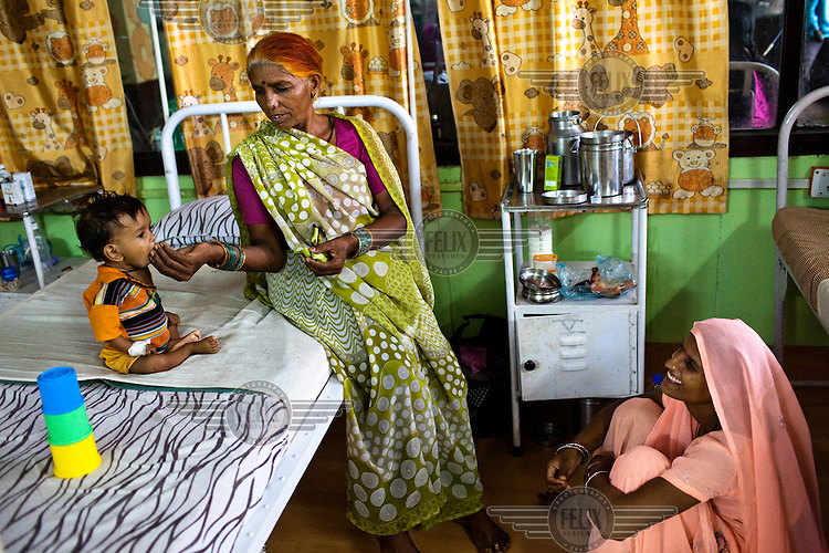 Rajeshwari feeds her 9 month old malnourished grandson Raj while her daughter looks on at the nutritional rehabilitation centre in the pediatric ward at Maharani Laxmibai Medical College in Jhansi. The Indian government spends $1.4 billion a year on programs that include weighing newborn babies, counseling mothers on healthy eating and supplementing meals, but none of this seems to be yielding results.