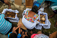 """Mayan peasants take care of dried-up bones of deceased family members during the bone cleansing ritual at the cemetery in Pomuch, Mexico, 27 October 2019. Every year on the Day of the Dead, people of Pomuch, a small Mayan community in the south of Mexico, visit the cemetery to take part in a pre-Hispanic tradition of cleaning of bones of their departed relatives (""""Limpia de huesos""""). People who die in Pomuch are firstly buried for three years in an above-ground tomb then the dried-up bodies are taken out, bones are separated, wrapped in a decorated cloth, put into a wooden crate, and placed on display among flowers for veneration."""