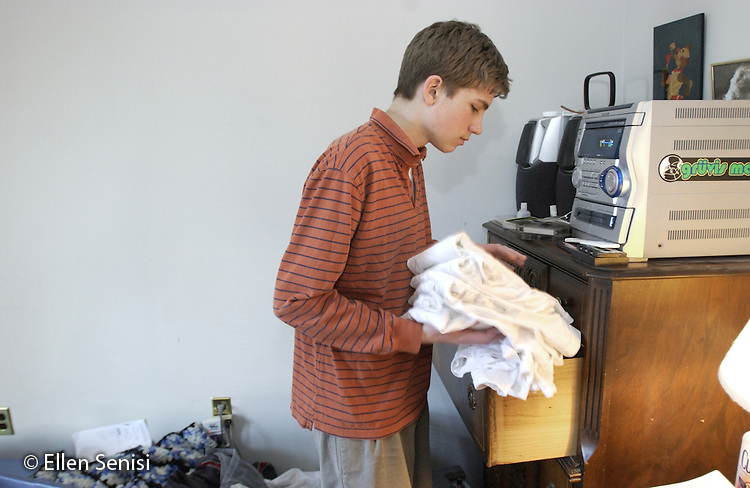 MR / Schenectady, NY. Boy (15) puts clean laundry away in his drawer as he cleans his bedroom. One of a series of photographs chronicling the growth and human development of the same person from infancy through to adulthood..MR: Sen3.©Ellen B. Senisi