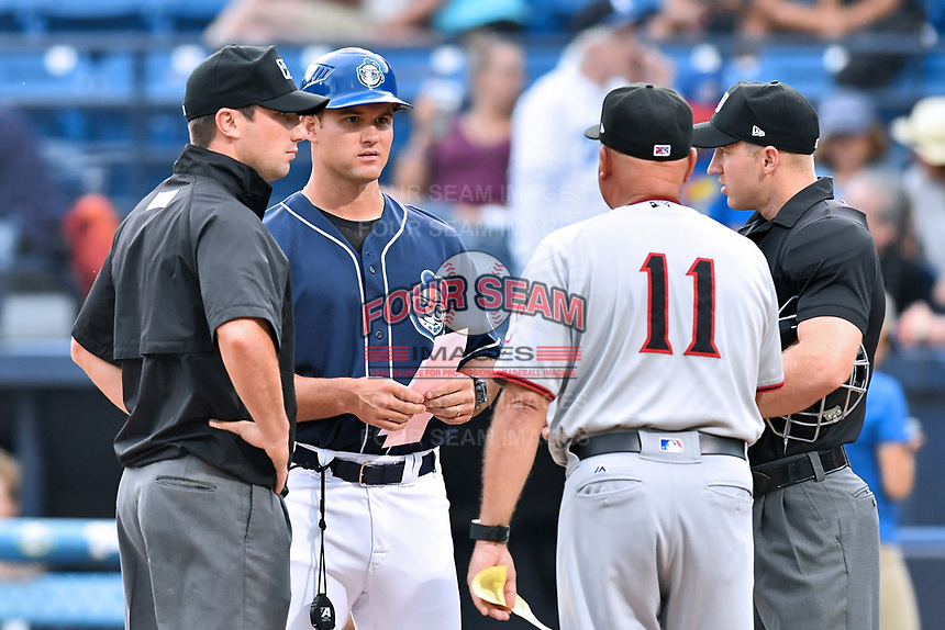 First base umpire Matthew Brown, Asheville Tourists manager Warren Schaeffer (13), Hickory Crawdads manager Spike Owen (11) and home plate umpire Mark Stewart before a game between the Crawdads and the Tourists at McCormick Field on July 13, 2017 in Asheville, North Carolina. The Tourists defeated the Crawdads 9-4. (Tony Farlow/Four Seam Images)