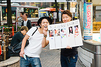 """Two young men in Shibuya. The poster reads """"If you were to become friends, who would you choose?"""""""