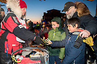 Aliy Zirkle gives away a dog bootie to a young fan in the finish chute in Nome after finishing in 15th place on Wednesday March 14th during the 2018 Iditarod Sled Dog Race.  <br /> <br /> Photo by Jeff Schultz/SchultzPhoto.com  (C) 2018  ALL RIGHTS RESERVED