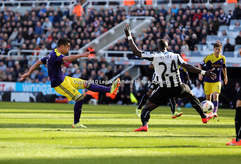 Pictured L-R: Pablo Hernandez of Swansea takes a shot at goal, marked by Cheik Tiote of Newcastle. Saturday 19 April 2014<br /> Re: Barclay's Premier League, Newcastle United v Swansea City FC at St James Park, Newcastle, UK.