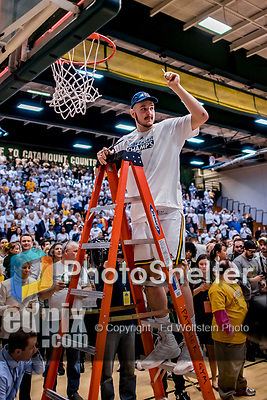 16 March 2019: University of Vermont Catamount Forward Ryan Davis, a Freshman from Schaumburg, IL, cuts himself a piece of net after a victory over the UMBC Retrievers in the America East Championship Game at Patrick Gymnasium in Burlington, Vermont. The Catamounts defeated the Retrievers 66-49, avenging their loss against the same team in last years' Championship Game. Mandatory Credit: Ed Wolfstein Photo *** RAW (NEF) Image File Available ***