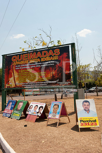 Canarana, Brazil. State Agiculture sign hoarding warning that it is illegal to burn rubbish and waste; also election posters.