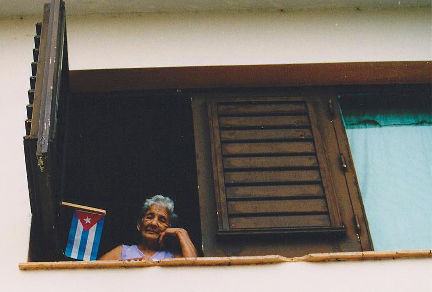A woman watches a parade pass below her window during May Day celebrations in Varadero, Cuba May 1, 2003. MARK TAYLOR GALLERY