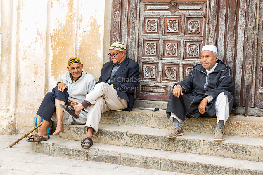 Fes, Morocco.  Three Old Men Resting on the Steps of the Andalusian Mosque, Fes El-Bali.