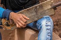 Morocco.  Teenage Amazigh Berber Musician Playing a Gimbrie.  Ait Benhaddou Ksar, a World Heritage Site.